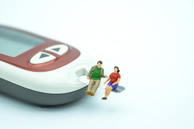 Miniatura de gordo homem e mulher figura sentada na tira de teste com medidor de glicose