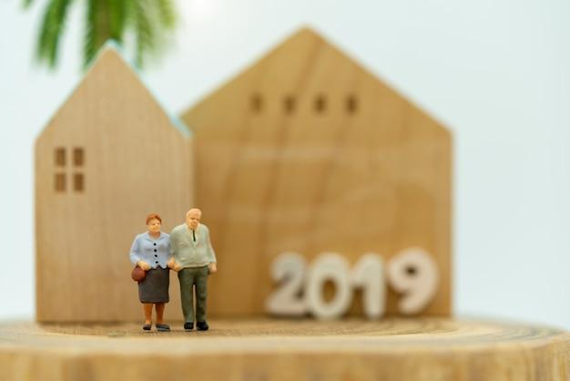 Miniatura de idosos em pé com casa