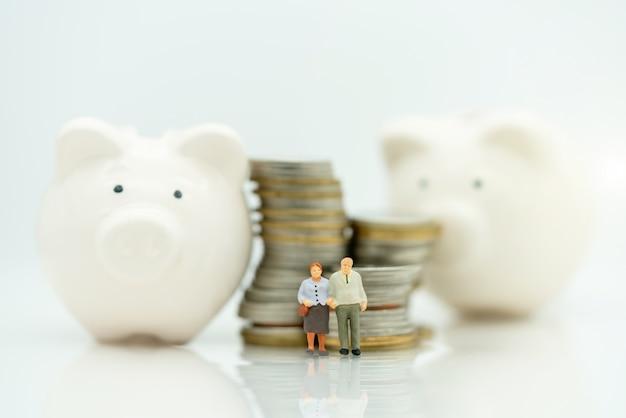 Miniatura de idosos em pé com pilha de moedas e cofrinho