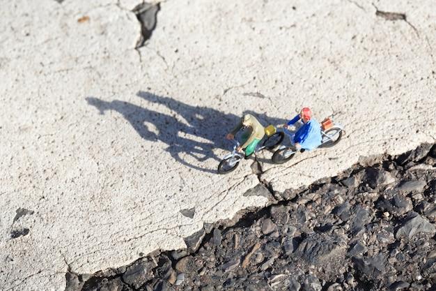 Miniatura de idosos felizes em um passeio de bicicleta na estrada rural em dia ensolarado.