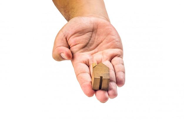 Miniatura de madeira da casa com a mão no fundo branco