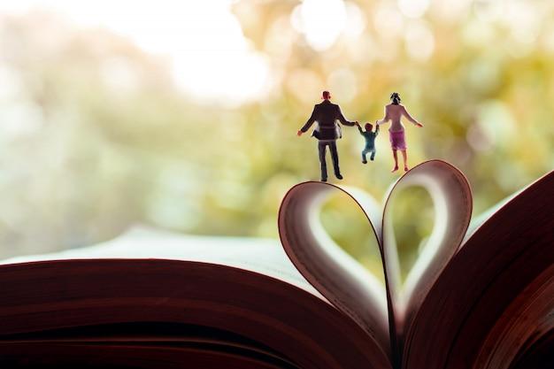 Miniatura de pai, mãe e filho de mãos dadas e caminhando em direção ao livro sobre um rolo de página como forma de coração