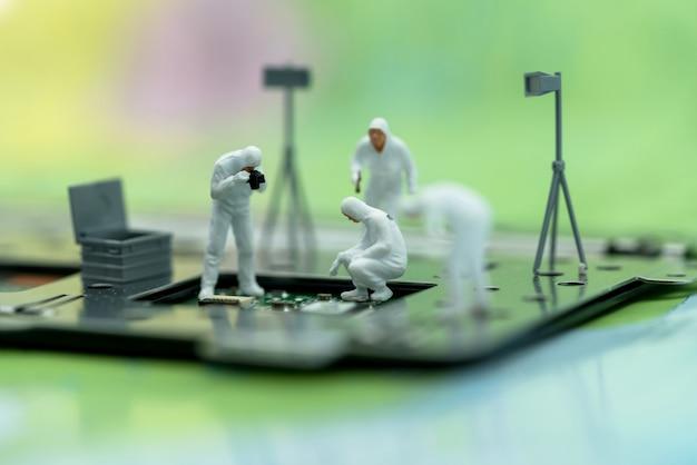 Miniatura de pessoas à procura de bugs no microchip
