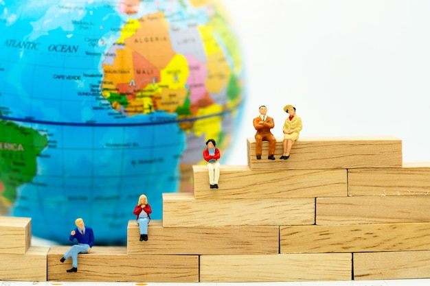 Miniatura de pessoas de negócios, sentado na caixa de madeira com o mundo