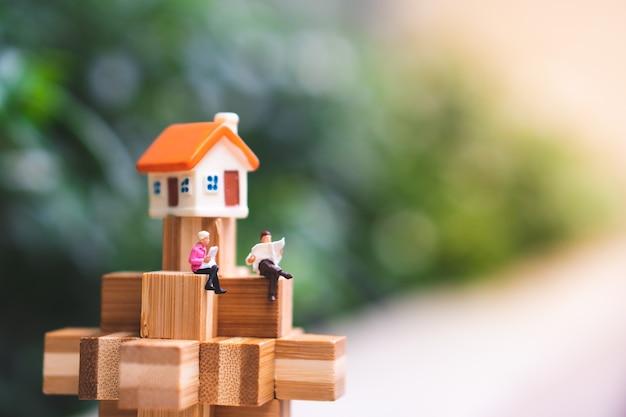 Miniatura de pessoas, homem e mulher sentada no bloqueio de madeira