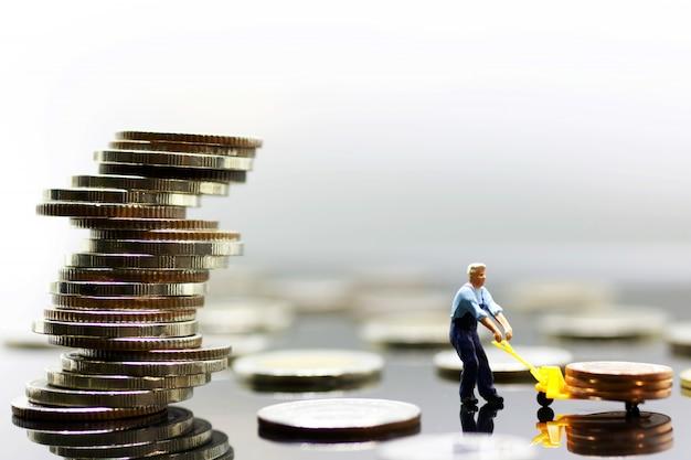 Miniatura de trabalhador transportar moedas para a pilha mais alta