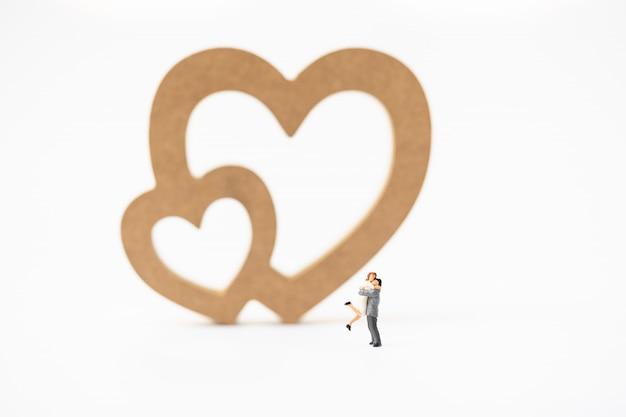 Miniatura de uma mulher e um homem apaixonado na frente do sinal de coração com copyspace