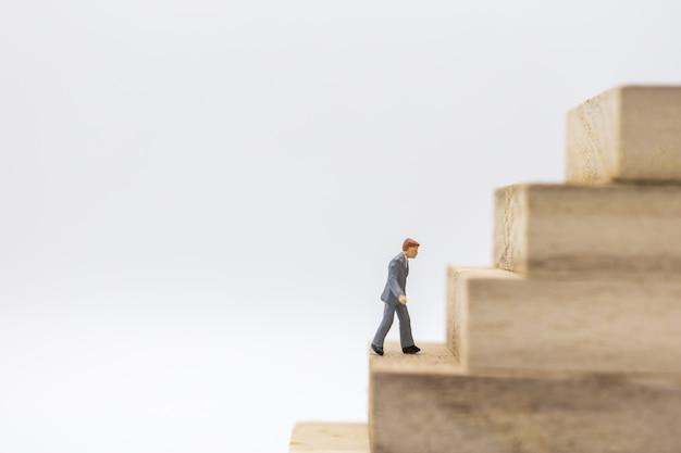 Miniatura do empresário andando para o topo da pilha de brinquedo de madeira do bloco