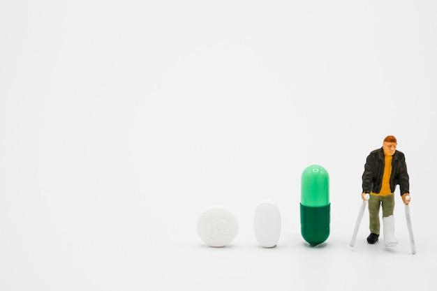 Miniatura do velho modelo de pernas quebradas ao redor com pílulas de medicina farmacêutica