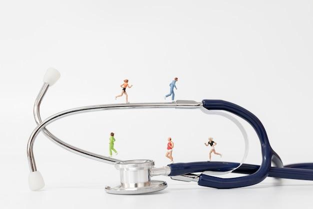 Miniatura pessoas correndo no estetoscópio