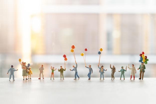 Miniatura pessoas: família feliz andando com balões