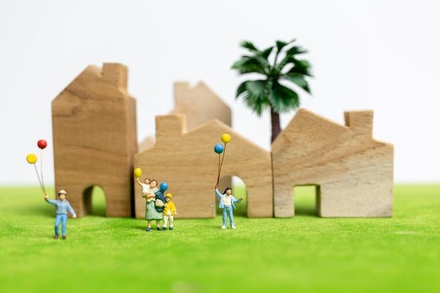 Miniatura pessoas: família feliz andando em campo com balões