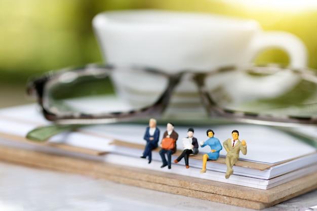 Miniatura pessoas lendo e sentado no livro com óculos.
