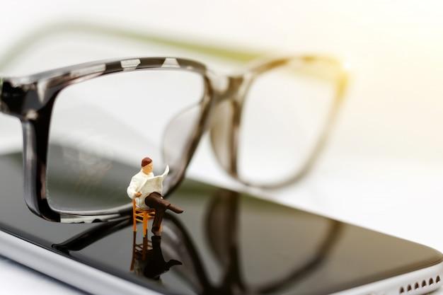 Miniatura pessoas lendo jornais com óculos.