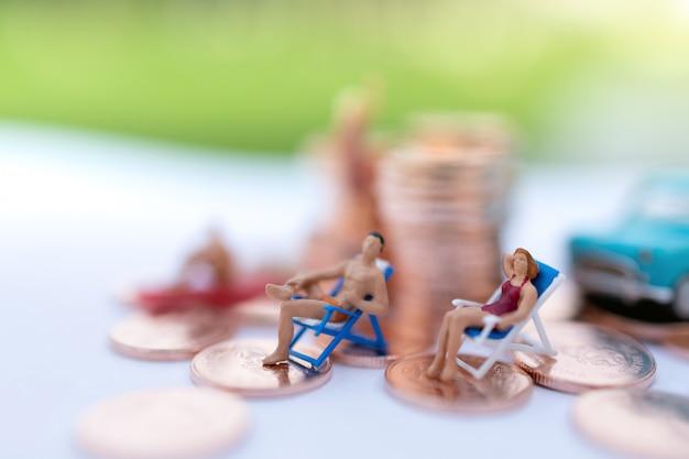 Miniatura pessoas sentadas na praia com moedas