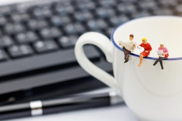 Miniatura pessoas sentadas na xícara de café com teclado e caneta.
