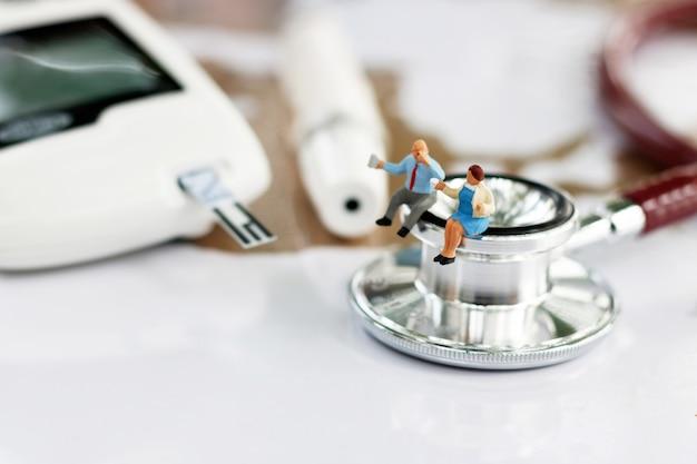 Miniatura pessoas sentadas no estetoscópio e glicose medidor de diabetes.