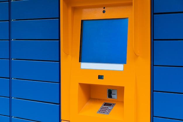 Minibank de caixa eletrônico laranja com tela copyspace em branco sobre fundo de azulejo de painel azul