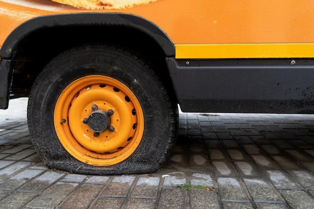 Minibus laranja vintage com uma roda plana.