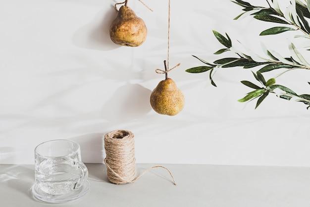 Mínima natureza morta de um copo de água e peras em uma mesa cinza.