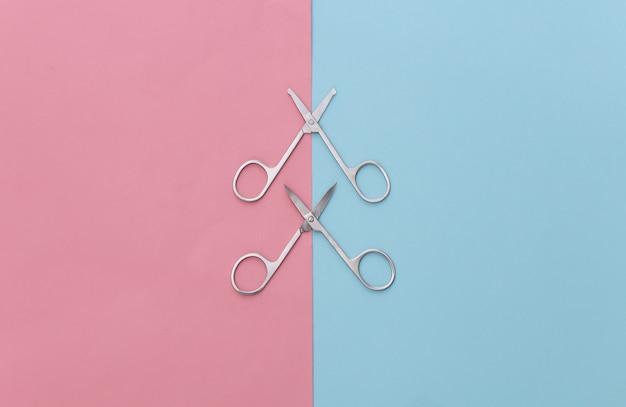Minimalismo de beleza. duas tesouras de manicure em rosa azul. cuidados com as unhas