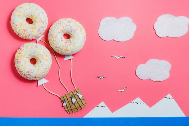 Minimalismo de comida criativa, donut em forma de aeróstato no céu rosa com nuvens, montanhas, vista superior, cópia espaço, viagens