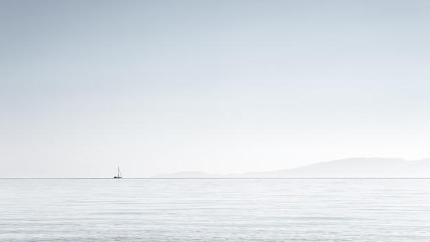 Minimalismo, imagem de um pequeno barco no horizonte, céu claro no mar egeu, halkidiki, grécia.