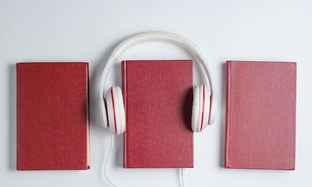 Minimalismo online ouvir o conceito de livros. audiobook livro com fones de ouvido em um fundo branco. vista do topo