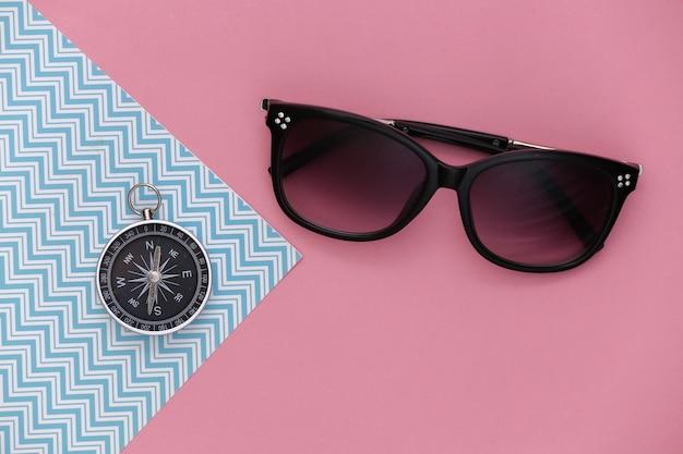 Minimalismo viajar plana leigos. bússola e óculos de sol em um fundo azul-rosa pastel. vista do topo