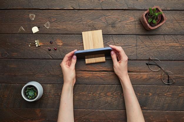 Mínimo acima, veja a postura plana de mãos femininas colocando o smartphone em pé sobre o plano de trabalho de madeira texturizado