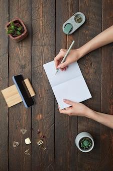 Mínimo acima, veja a postura plana de mãos femininas, escrevendo no planejador sobre o fundo do local de trabalho de madeira texturizada.