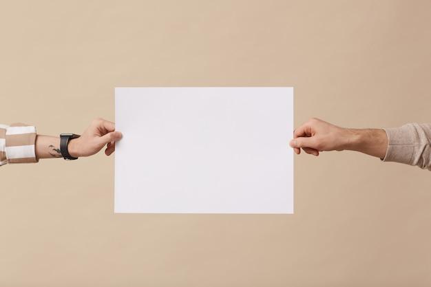 Mínimo close-up de duas mãos segurando um cartaz em branco contra um fundo bege no estúdio, copie o espaço