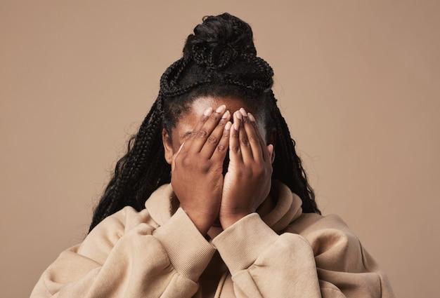 Mínimo close-up retrato de jovem afro-americana escondendo o rosto enquanto posava em um fundo bege neutro em estúdio, copie o espaço