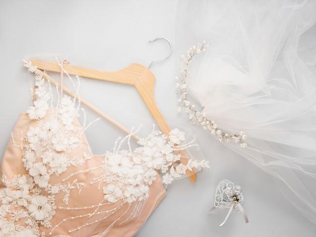 Mínimo plano leigos com vestido de noiva no cabide e véu com miçangas no fundo claro