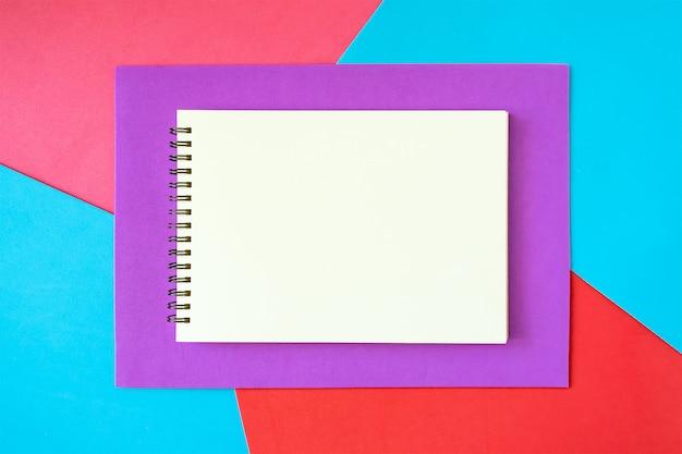 Mínimo, pop art, maquete abstrata, vívida com o bloco de notas branco sobre fundo brilhante