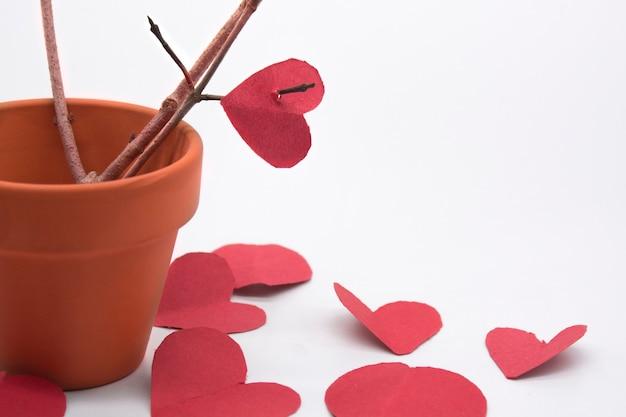 Minipote de argila com galhos de árvores marrons e corações vermelhos ao redor do pote para o dia dos namorados