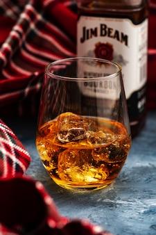 Minsk, bielorrússia - 31 de outubro de 2018: garrafa e copo jim beam é uma das marcas mais vendidas de bourbon do mundo, produzida pela beam inc. em clermont, kentucky.