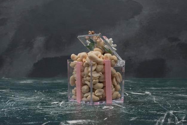 Minúscula caixa cheia de nozes na mesa de mármore.