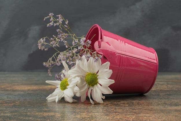 Minúsculo balde rosa com buquê de flores na superfície de mármore.
