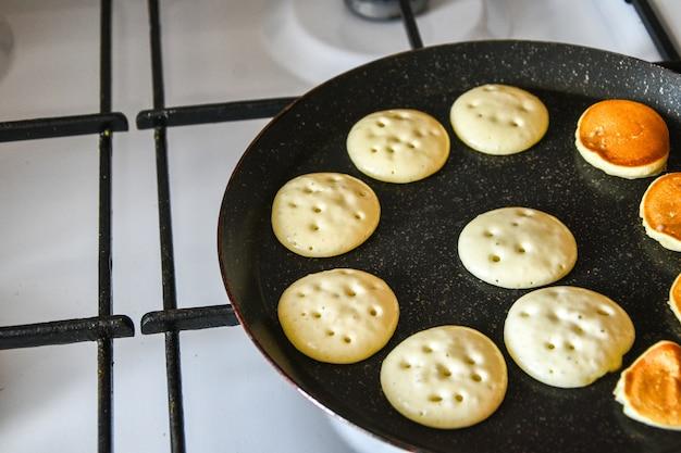 Minúsculos cereais de panqueca colocados em quarentena comidas populares. mini panquecas são fritas em uma panela na cozinha. processo de cozimento. fritura de fotos ao vivo