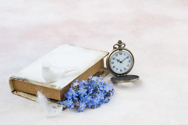 Miosótis em um livro, relógios de bolso, penas e uma estatueta de porcelana de um pássaro