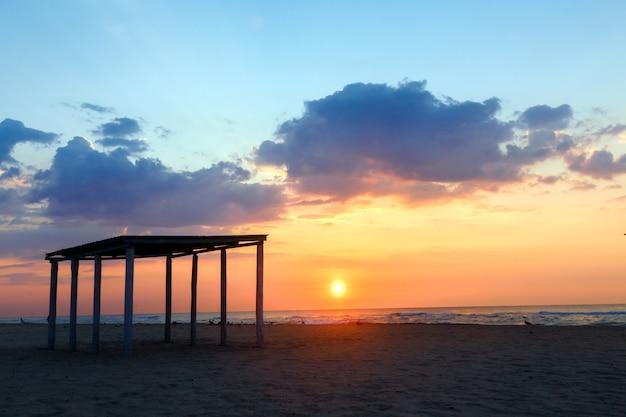 Miradouro da silhueta em uma praia arenosa vazia em um fundo do por do sol.