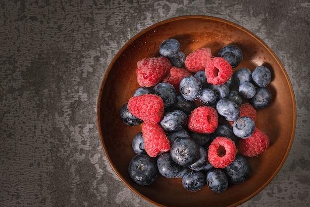 Mirtilo e framboesa em um prato de barro. frutas cruas se misturam de perto. frutas frescas de verão.