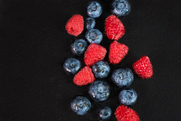 Mirtilo e framboesa isoladas no fundo preto. mistura de frutas crus isolada.