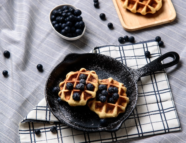 Mirtilos caseiros waffles e gelo em um prato que se parece com uma panela.