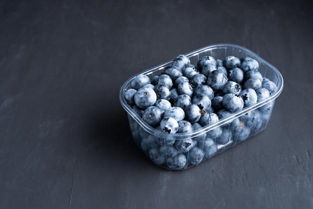 Mirtilos crus suculentos saborosos em um recipiente plástico. embalagem para bagas em um supermercado nas prateleiras das lojas.