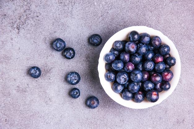Mirtilos deliciosos em uma tigela redonda branca sobre um fundo de gesso violeta. configuração plana.