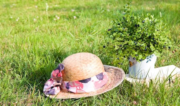 Mirtilos e chapéu de verão na grama verde