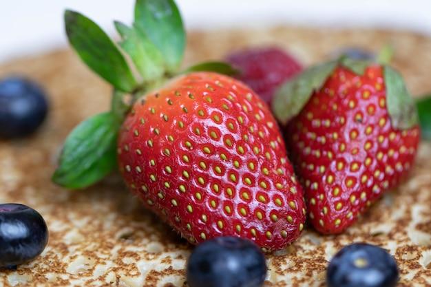 Mirtilos e morangos maduros e suculentos repousam sobre uma deliciosa panqueca. prato nacional da cozinha russa bliny com frutas frescas.