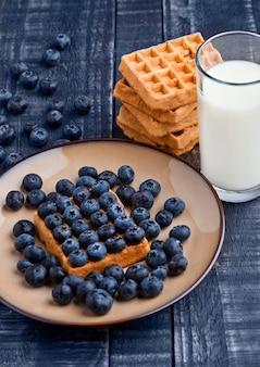 Mirtilos e waffles no prato com copo de leite